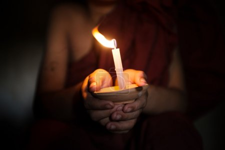 Little monk holding a candlelight...
