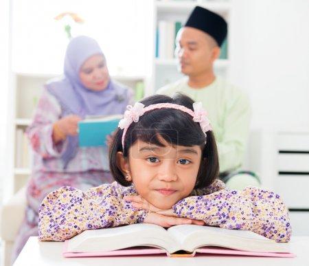 Photo pour Une musulmane lisant un livre. Famille malaise à la maison. Parents et mode de vie des enfants d'Asie du Sud-Est . - image libre de droit