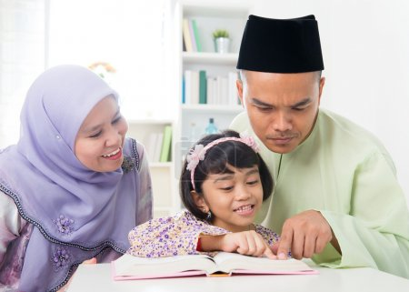 Photo pour Les parents musulmans malais enseignent à l'enfant à lire un livre. Famille sud-est asiatique à la maison . - image libre de droit