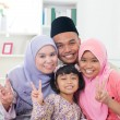 Happy Asian family at home. Muslim family showing ...