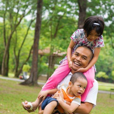 Photo pour Famille d'Asie du Sud-Est s'amuser au parc vert en plein air. Belle famille musulmane jouant ensemble . - image libre de droit