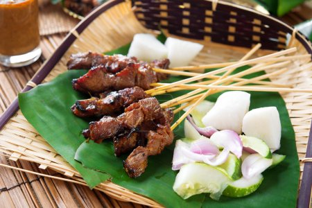 Photo for Satay or sate, skewered and grilled meat, served with peanut sauce, cucumber and ketupat, Malaysia or Indonesia food. Traditional Malay food. Hot and spicy Malaysian dish, Asian cuisine. - Royalty Free Image