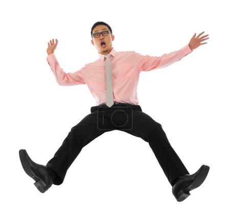 Asian businessman falling backwards