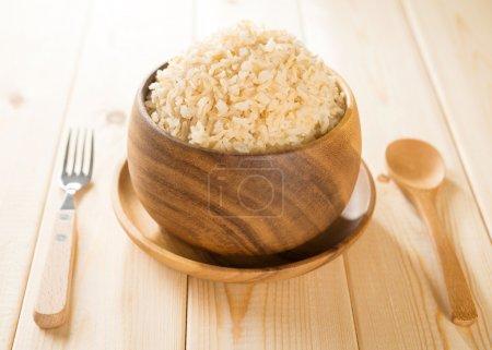 Photo pour Inde cuit basmati bio riz brun dans un bol en bois sur la table à manger. - image libre de droit