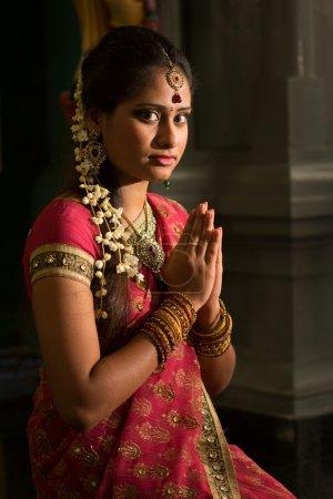 Photo pour Jeune Indienne en robe sari traditionnelle priant dans un temple hindou . - image libre de droit