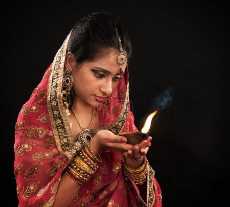 Photo pour Belle jeune femme indienne en robe de sari traditionnelle tenant une lampe à huile diwali, isolée sur fond noir . - image libre de droit