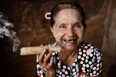 Photo pour Heureuse vieille femme asiatique ridée fumant du tabac traditionnel. Bagan, Myanmar . - image libre de droit