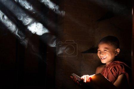 Asian little monk reading book
