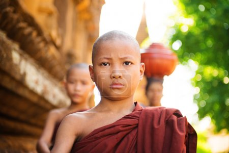 Photo for Young Buddhist monks walking morning alms in Old Bagan, Myanmar - Royalty Free Image