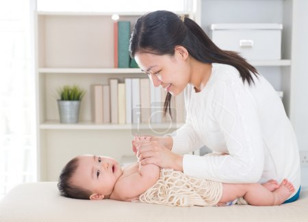 Photo for Baby massage. Asian mother massaging baby hands at home. - Royalty Free Image