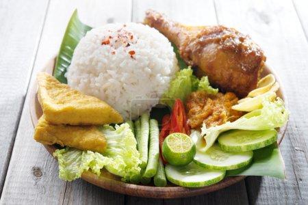 Photo pour Célèbre cuisine traditionnelle indonésienne. Délicieux nasi ayam penyet avec sambal belacan. Frais chaud avec fumée de vapeur . - image libre de droit