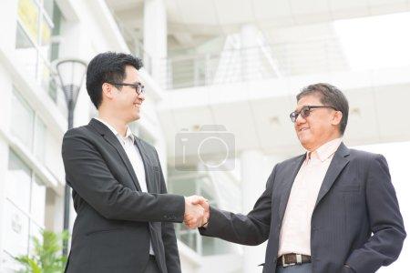 Photo pour Poignée de main des hommes d'affaires asiatiques. Senior chef de la direction main secouer avec jeune cadre. immeuble moderne de fond d'architecture. - image libre de droit