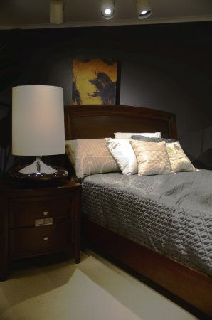 Home interior scene featuring a modern bedroom setting with dark red furniture accents