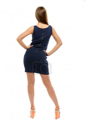 Slim girl in a dress stands back