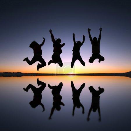 Photo pour Un groupe de jeunes amis heureux sautant à Solar de Uyuni, Bolivie - image libre de droit