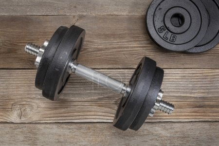 Photo for Exercise weights - iron dumbbell with extra plates on a wooden deck - Royalty Free Image