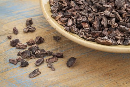 Raw cacao nibs in a small ceramic bowl against gru...