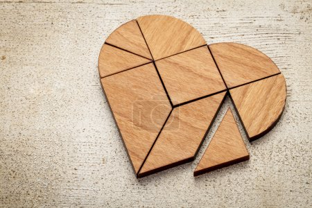 Photo for Heart version of tangram, a traditional Chinese Puzzle Game made of different wood parts to build abstract figures from them, on white painted barn wood - Royalty Free Image