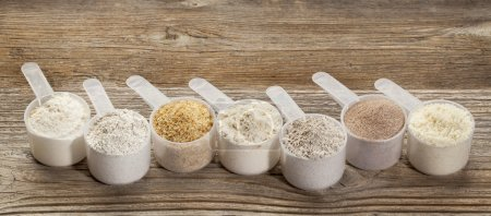 Photo for A row of measuring scoops of gluten free flours - almond, coconut, teff, flaxseed meal, whole rice, brown rice, buckwheat - Royalty Free Image