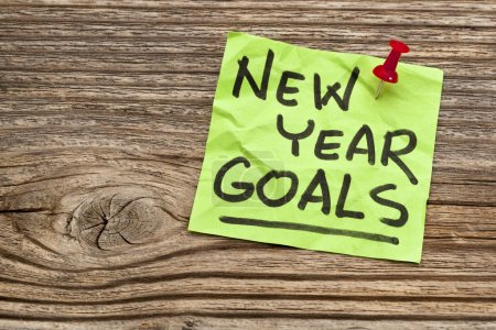 Photo for New Year goals - handwriting on a sticky note against grained wood - Royalty Free Image