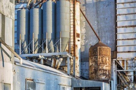 Photo pour Arrière-plan industriel extérieur de l'ancien élévateur à grain avec tuyaux, conduits, échelles et goulottes - image libre de droit