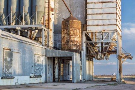 Photo pour Vieil ascenseur à grain avec tuyaux, conduits, échelles et chutes, un paysage rural éloigné du nord du Colorado - image libre de droit