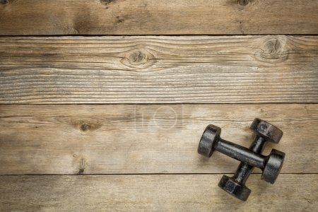 Photo for A pair of vintage iron rusty dumbbells on a grained wood background with a copy space - Royalty Free Image