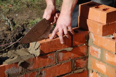 Photo for Closeup of bricklayer building a house extension. Photo shows man holding trowel while laying bricks. - Royalty Free Image
