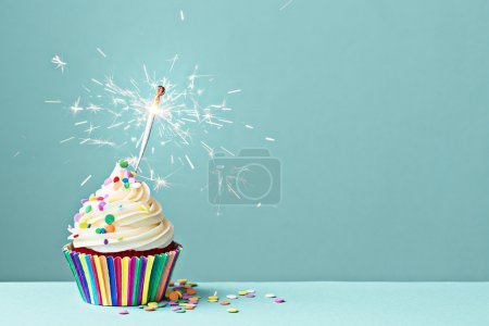 Photo for Cupcake decorated with colorful sprinkles and a sparkler - Royalty Free Image