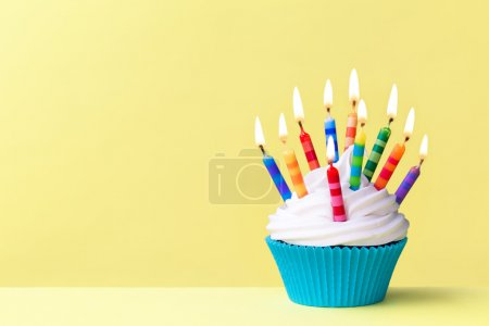 Photo for Birthday cupcake against a yellow background - Royalty Free Image