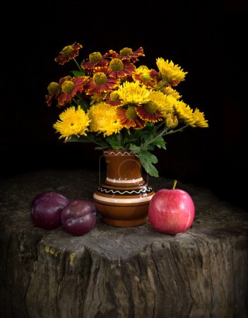 Photo pour Nature morte dans un style champêtre avec éclairage nocturne mystérieux. Nosegay de chrysanthèmes jaune vif et rouge Gaillardias dans un vase peint en argile se dresse sur tronc d'arbre près de fruits mûrs sur fond noir - image libre de droit