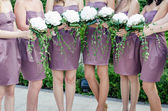 Row of bridesmaids with bouquets at wedding ceremony