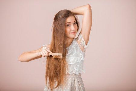 Photo pour Belle fille peigne ses cheveux sur fond rose - image libre de droit