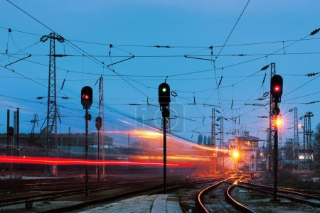 Night shot of railway station with curving track a...