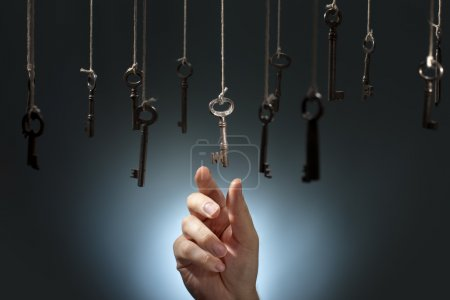 Hand choosing a hanging key amongst other ones....