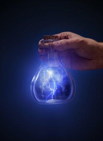 Photo pour Homme tenant une vieille bouteille avec des éclairs à la main . - image libre de droit