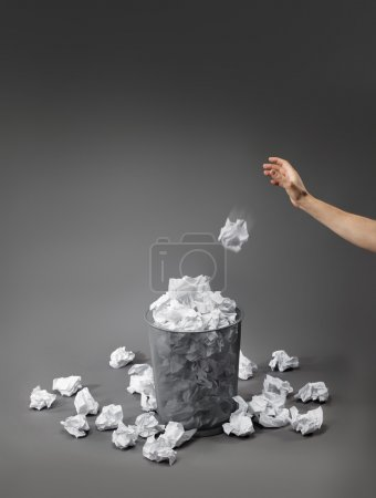 Photo for Hand throwing a crumpled paper into a waste paper basket. - Royalty Free Image