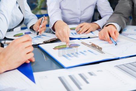 Photo pour Groupe de travail de l'équipe d'affaires pendant la conférence discutant le diagramme financier, les diagrammes d'affaires, assis, pointant du doigt le document de graphique - image libre de droit