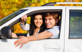 Young happy couple driving