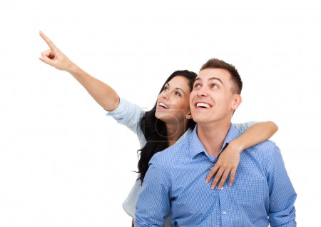 Young happy couple pointing finger to copy space