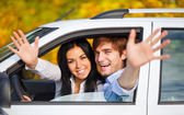 Young happy couple driving in car