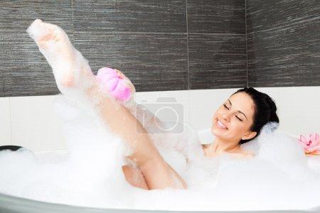 Woman washing leg with pink sponge