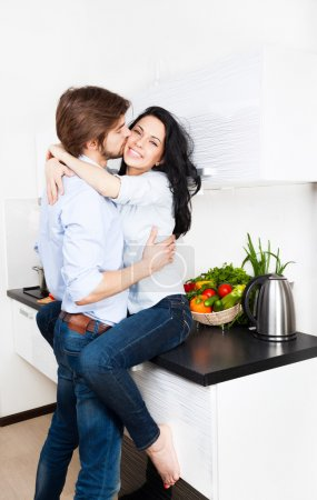 Couple kissing at their kitchen