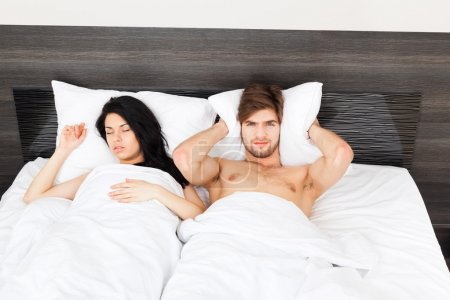 Couple in bed, snoring woman, man can not sleep