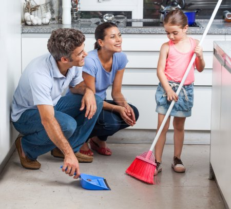 Father, mother and daughter sweeping floor