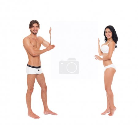 Couple in swimsuits showing blank board