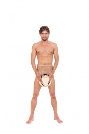 Naked man covering genitals by hat