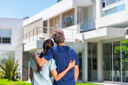 Photo for Couple embracing in front of new big modern house, outdoor rear view back looking at their dream home - Royalty Free Image