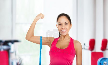 Fitness woman measures her biceps