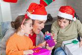 Otec se dvěma dětmi otevřené vánoční dárky